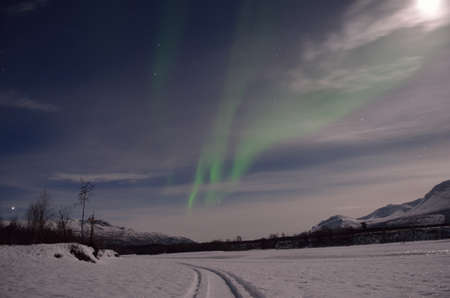 artic circle: aurora borealis, northern light over a frozen snowy river bed with full moon and majestic mountain Stock Photo