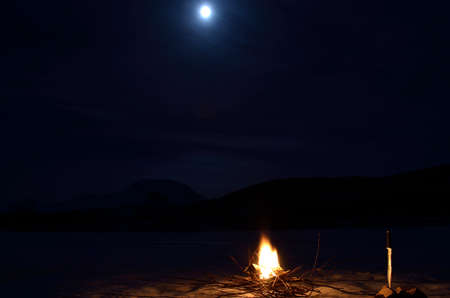 artic circle: burning fire on frozen river bed with majestic snowy mountain and full moon in the background Stock Photo