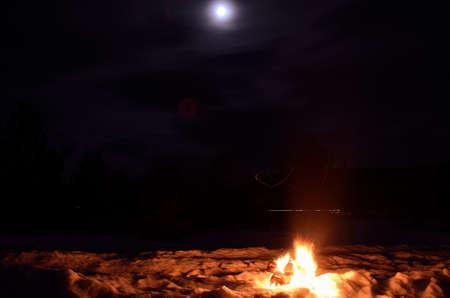 log fire: caminetto betulla sulla neve d'inverno in una notte di luna piena oscura