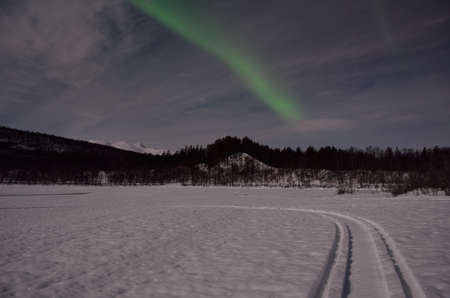 artic circle: aurora borealis, northern light over winter river landscape at night with full moon lighting Stock Photo