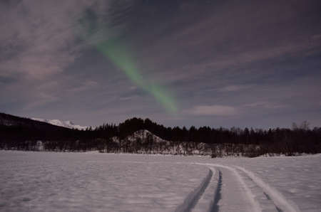 aurora borealis, northern light over winter river landscape at night with full moon lighting photo