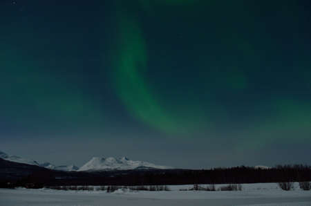 ionosphere: aurora borealis, northern light over winter landscape and snowy mountain