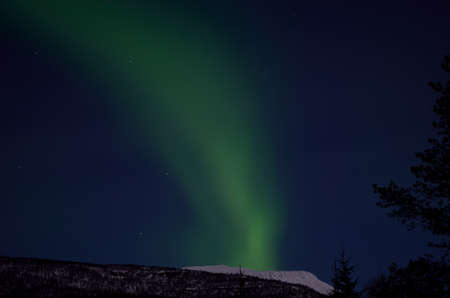 ionosphere: strong aurora borealis, northern light emerging over snowy mountain peak in winter