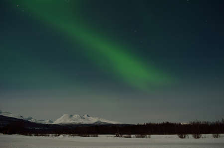 artic circle: aurora borealis, northern light over winter landscape and snowy mountain