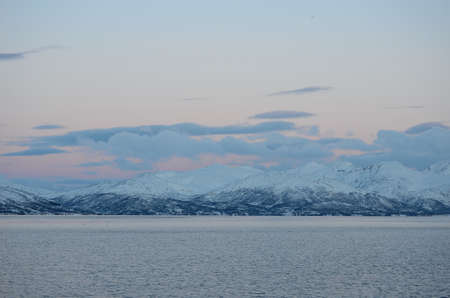 artic circle: majestic snowy mountain with colourful sunset sky and beautiful cloud formation with cold fjord water underneath in wintertime