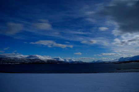 range of motion: Deep serene white mountain range behind vibrant blue fjord in easter time
