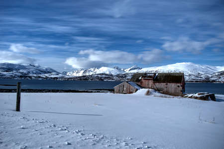 Vivid old barn on snowy field with blue fjord and white mountain  photo