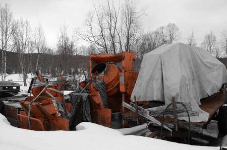 Heavy duty orange cement mixer in scrap yard photo