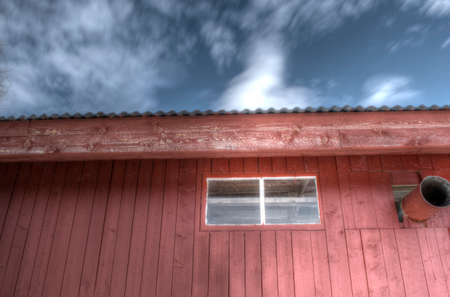 red barn: Red barn wall with blue spring sky and small clouds