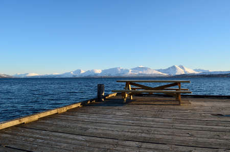 atmospheric: old wooden bench on pier end with snowy mountain, blue sky and fjord