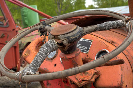 outside machines: old rusted and weathered tractor steering wheele