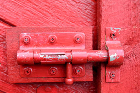 burgundy colour: bolt lock on red door macro photo Stock Photo