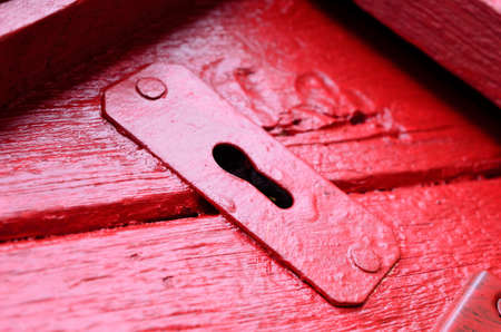 red door: red door with old key hole macro Stock Photo