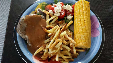 corncob: Beef, chips, peppersauce, corncob and salad dinner on plate