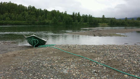 beside: Row boat on river side beside salmon river in summer Stock Photo