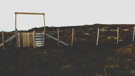 grazing land: Old fence and wooden gate at grazing pasture land