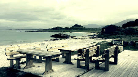 Wooden benches on patio beside white sand beach, blue fjord and mountain landscape in vesteraalen