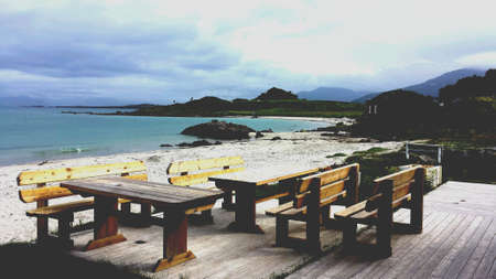 beside: Wooden benches on patio beside white sand beach, blue fjord and mountain landscape in vesteraalen