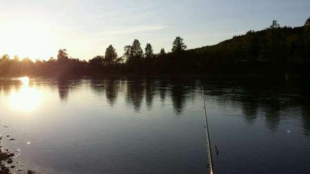 fishingpole: Fishingpole and salmon fisherman wading in river maalselv troms in autumn Stock Photo