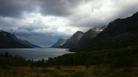 dark: Tall mountain valley with blue fjord at bottom in the arctic circle early autumn Stock Photo