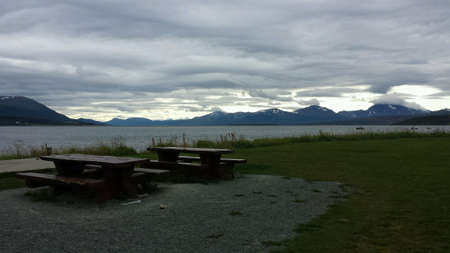 Wooden bench beside fjord with tromsoe city island