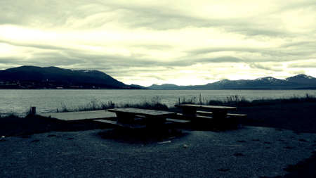Wooden bench beside fjord with tromsoe city island in background