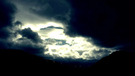dark skies: Dark clouds over mountains with small patches of blue sky and sunshine Stock Photo