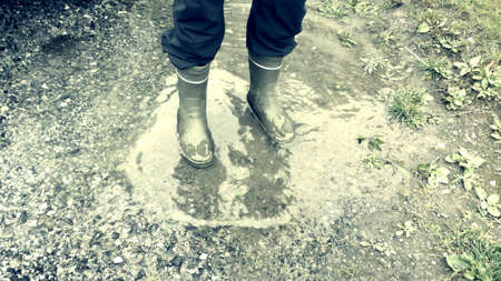 man: Man jumping in puddle with rubber rain boots Stock Photo