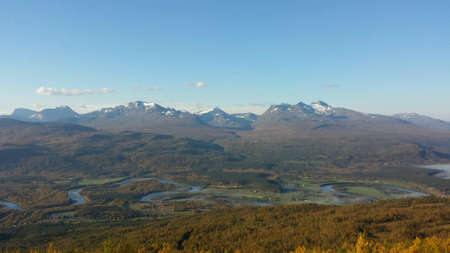 bright: Snowy peaks, blue sky, twisted river maalselv and yellow autumn birch tree forest in the deep north