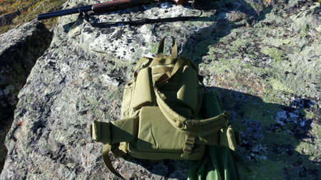 net: Shotgun, backpack and grouse bird in net on boulder during groude bird hunting season in autumn Stock Photo