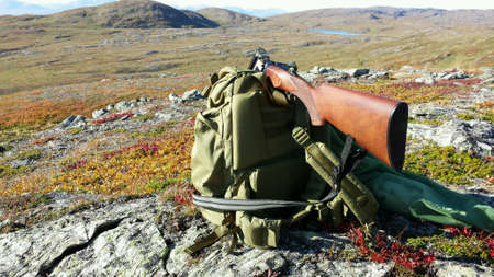 backdrop: Shotgun on green backpack and grouse bird in hunting net with mountain landscape backdrop in autumn