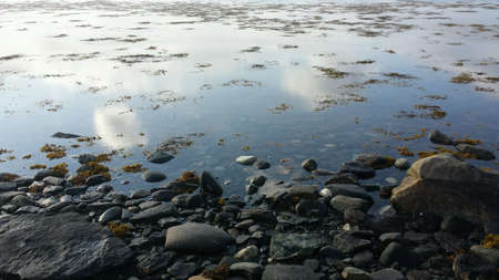 reflective: Cloud and blue sky reflection in calm fjord water surface in autumn sunshine Stock Photo
