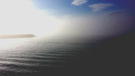 surface: Stone pier into blue fjord with thick sea fog blowing over ocean surface Stock Photo