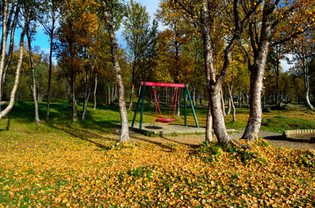 swing set: vibrant autumn forest with playground swing set and hiking trails Stock Photo