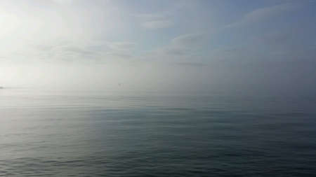 shrouded: Blue ocean landscape shrouded in sea fog and mist with autumn sunshine and blue sky patches