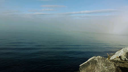 shrouded: Blue ocean landscape shrouded in sea fog and mist with autumn sunshine, blue sky and massive boulder Stock Photo