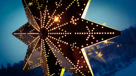 glow: Warm glowing christmas star in window with cold winter snowy landscape in background
