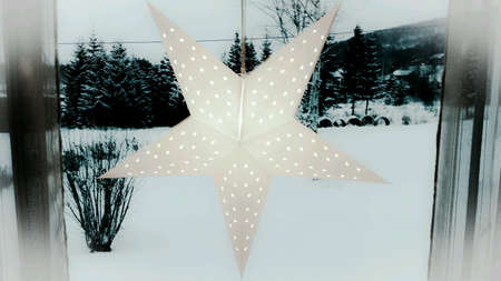 glow: Cold christmas star in window with snowy forest background Stock Photo