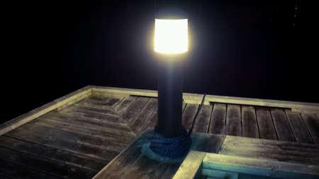 metal: Metal light pole on wooden walkway at sea