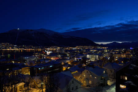 mainland: tromso city at winter snowy night with light,traffic,fjord and motion with mainland in background Editorial