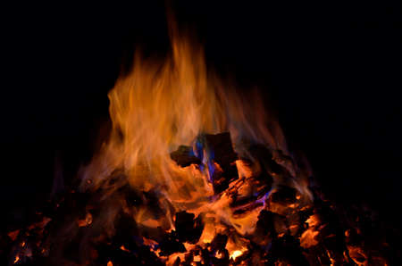 ember: beautiful red hot glowing ember pile with colorful flames in winter night