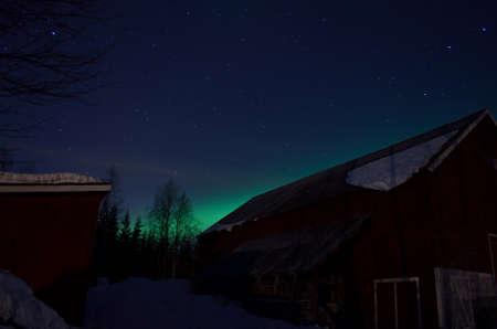 barns winter: aurora borealis over red barn with bright stars Stock Photo