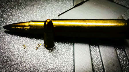 9mm ammo: Standing pistol bullet and laying down rifle bullet on plastic case macro photo