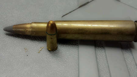 metal: Standing pistol bullet and laying down rifle bullet on plastic case macro photo
