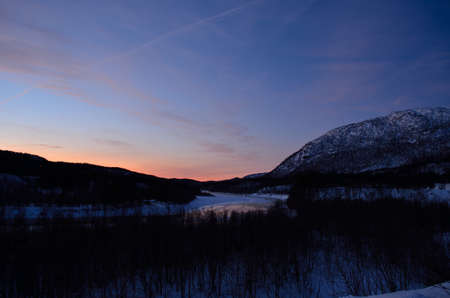 vibrance: vibrant sunset sky over mountain forest and icy river in winter