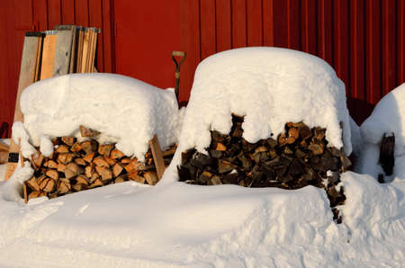 stack of firewood: snow covered firewood stack Stock Photo