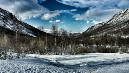 excersise: Wonderful mountain valley landscape in snowy winter wonderland with tromsoe city in the background