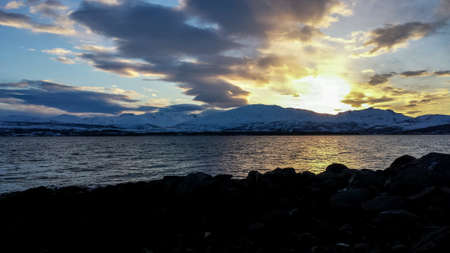surface: Golden sunny sunset over snowy mountain range with reflection on sea surface