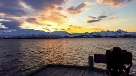surface: Sunny sunset over snowy mountain range with reflection on sea surface from wooden pier with camera