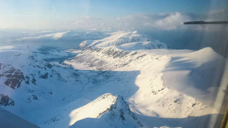 small plane: Majestic snowy mountain view in northern norway from small plane Stock Photo